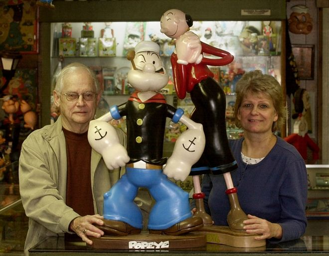Ernie Schuchert, left, nephew to J. William Schuchert, the inspiration for Wimpy, a character from the Popeye comic strip, and Laurie Randall, right, co-owner of Spinach Can Collectibles and the Popeye Museum, pose inside the museum in downtown Chester, Ill., Wednesday, Jan. 14, 2004. Saturday, Jan. 17, is the 75th anniversary of Popeye the Sailor Man's comic-strip debut. (AP Photo/Charles Rex Arbogast)